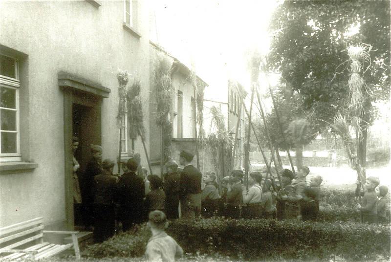 Dotzen an Seibert's Haus - Die Kinder, die beim Holzsammeln für das Martinsfeuer geholfen haben, gehen singend von Haustür zu Haustür und sammeln als Lohn Süßigkeiten und Geld.