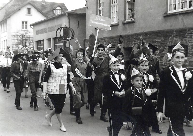 De Zuch kütt! - Karnevalsumzug ca. 1960 - im Vordergrund rechts: Prinzenelferat Werner Marquardt, Hansi Zimmermann, Karl-Willi Engels und Hans-Peter Reuschenbach (Beutel), und am Fenster: Frau Hesseler