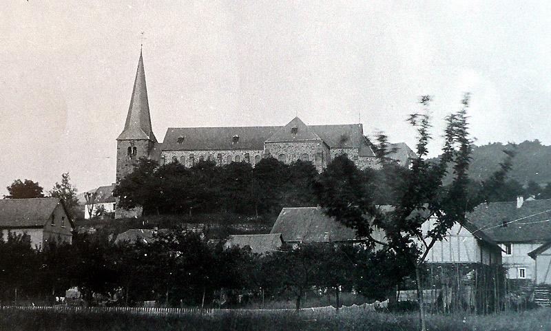 """Neue Pfarrkirche um 1900 - links das Kaufhaus Scheid und rechts Gasthaus """"Zum Schützenhof"""""""